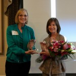 Nancy Blanton, last year's honoree, presents the Georgina MacDougall Davis Founder's Award to Whitney Mason (right).